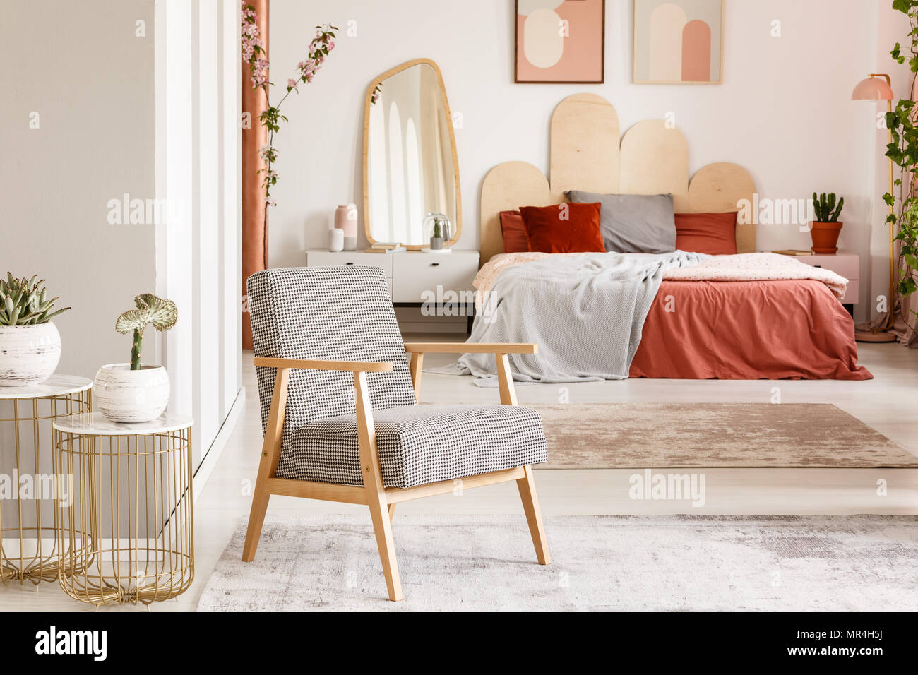 Patterned wooden armchair next to gold table in orange bedroom ...