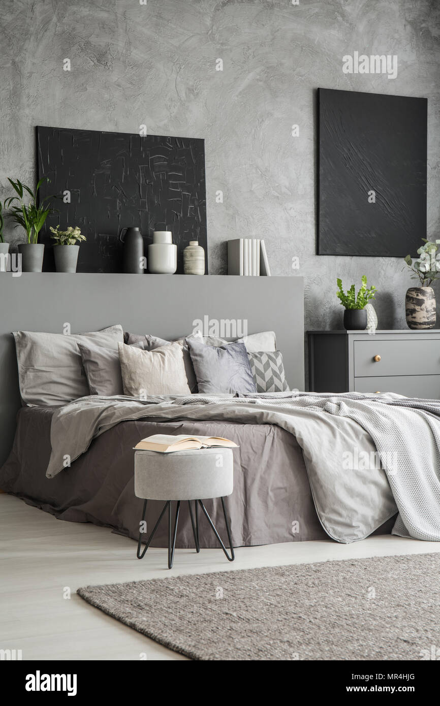 Parete Grigia Camera Da Letto book on stool next to bed in grey bedroom interior with