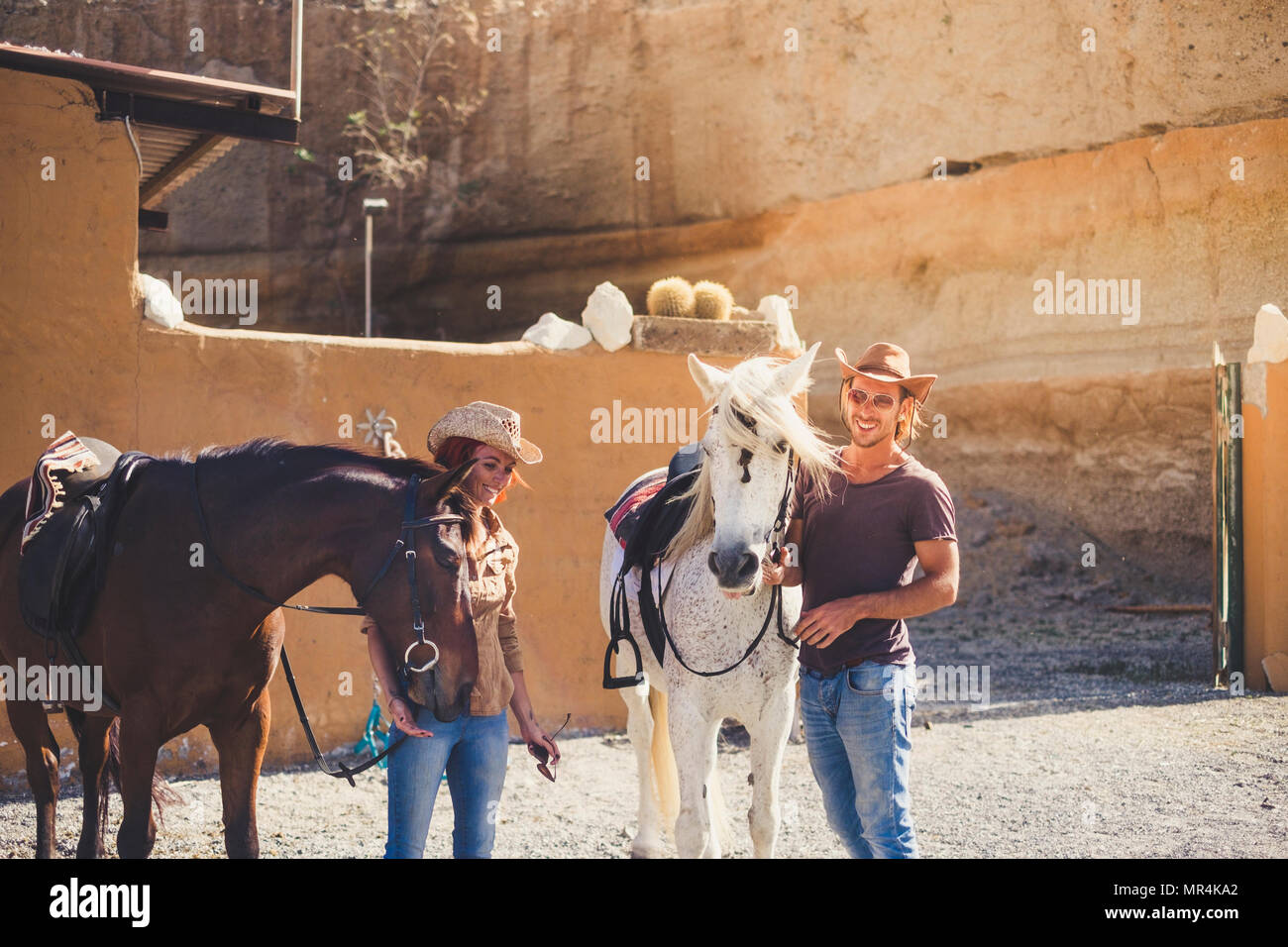 alternative lifestyle full contact with nature and animals in a ranch for a young and beautiful man and woman with horses. sunny day for freedom and d - Stock Image