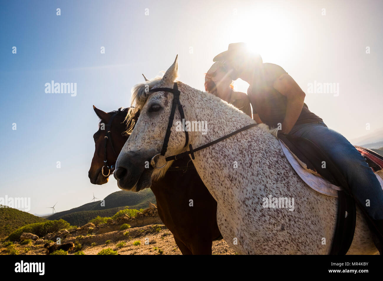 love scene between young beautiful coule riding two nice horses in the nature. windmill for green energy and better future on the background. alternat - Stock Image