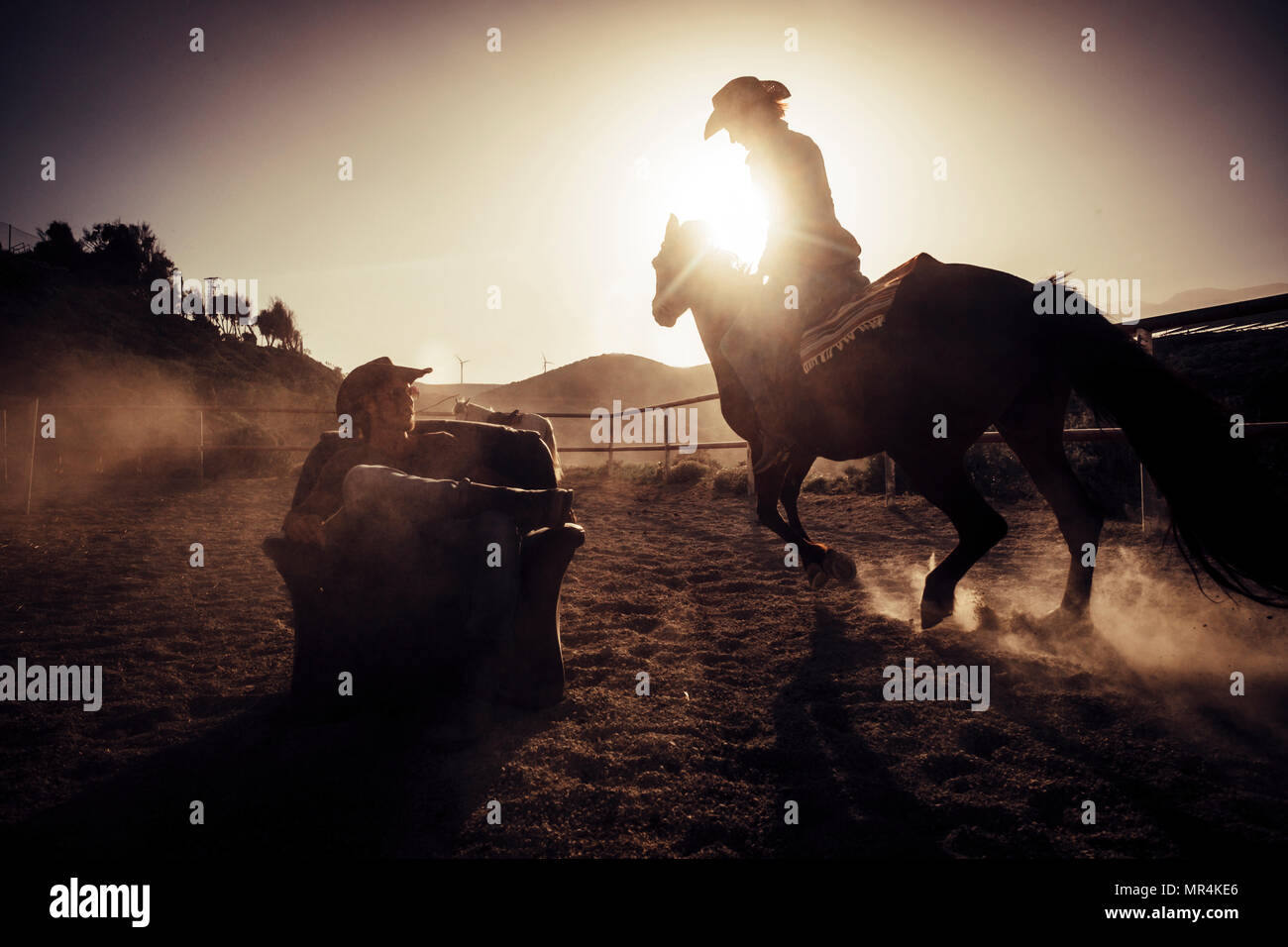 hero concept dramatic and advertising style image for cowgirl making dust riding a horse near a cowboy sit down on a chair in the middle of the track. - Stock Image