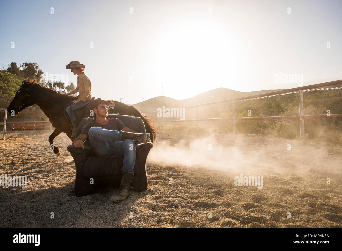 couple of beautiful man and woman together. she rides a horse making dust with speed and he stays sit down on the chair in the middle of the track - Stock Image