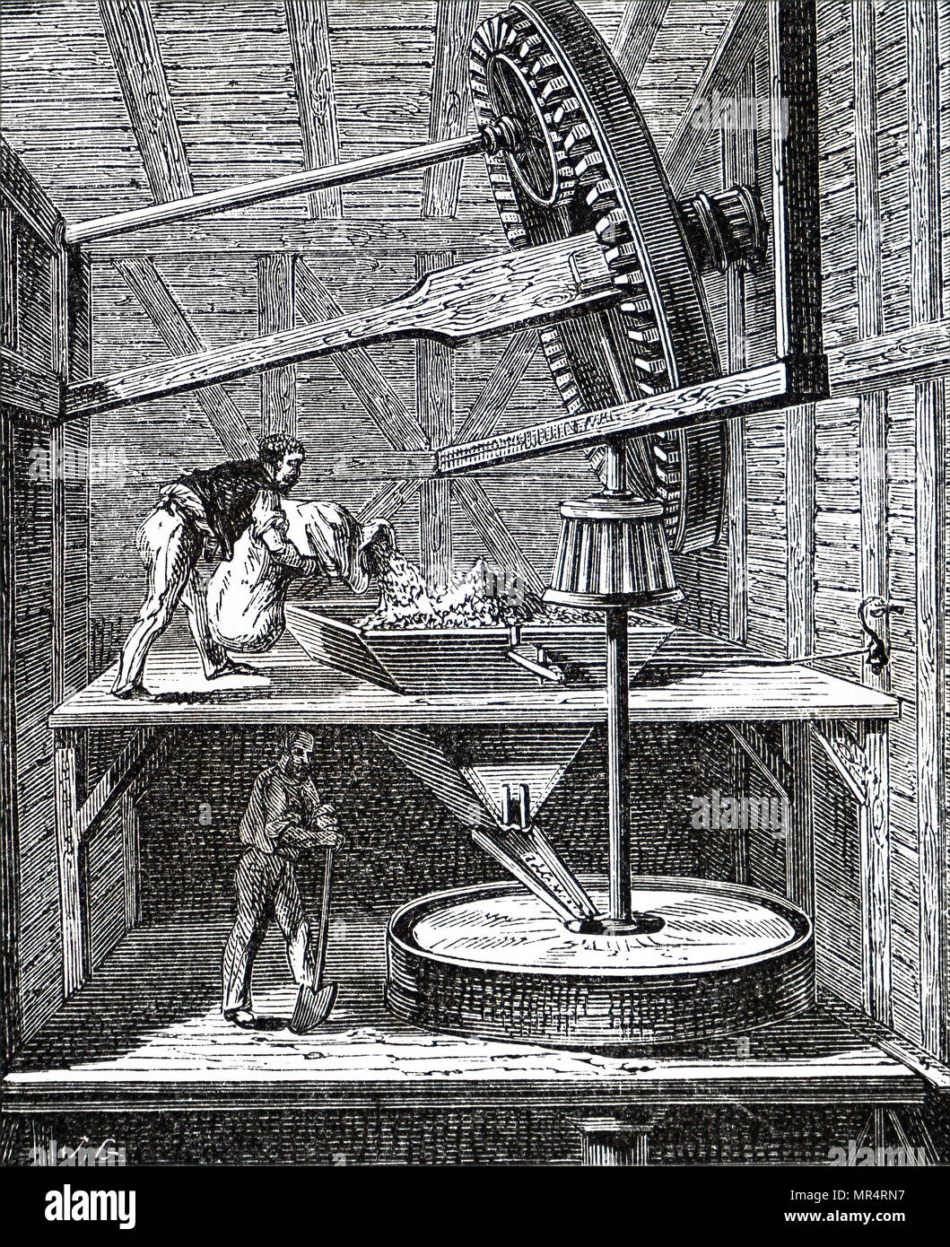 Sectional view of a windmill used to grind corn. On the upper floor the miller is feeding grain into the hopper which takes it to the centre of the millstone where it is ground into flour. Dated 19th century - Stock Image
