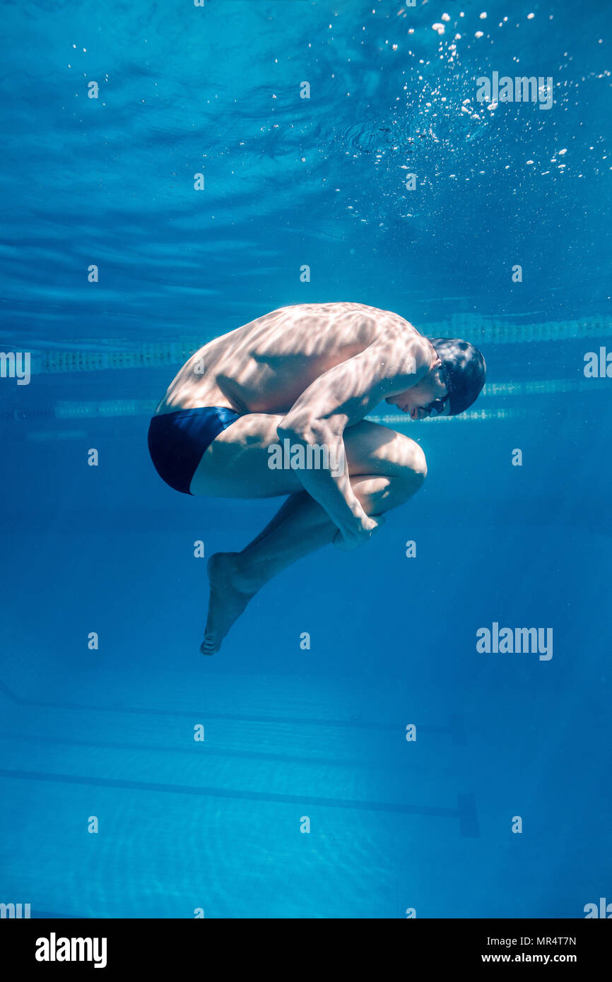 underwater picture of male swimmer in cap and goggles - Stock Image