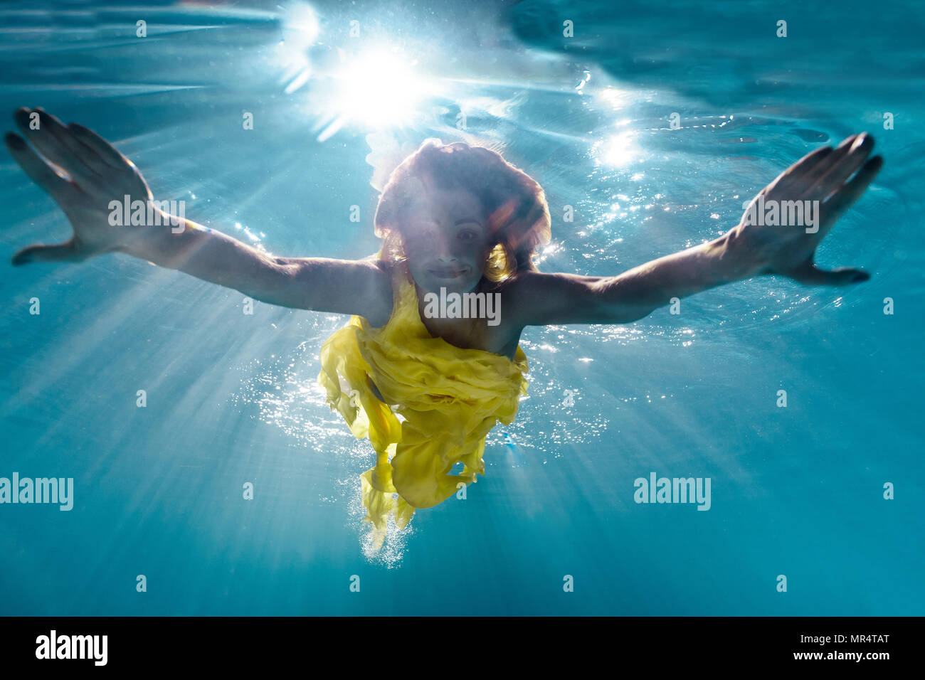 0324686419 underwater picture of beautiful young woman in dress swimming in swimming  pool