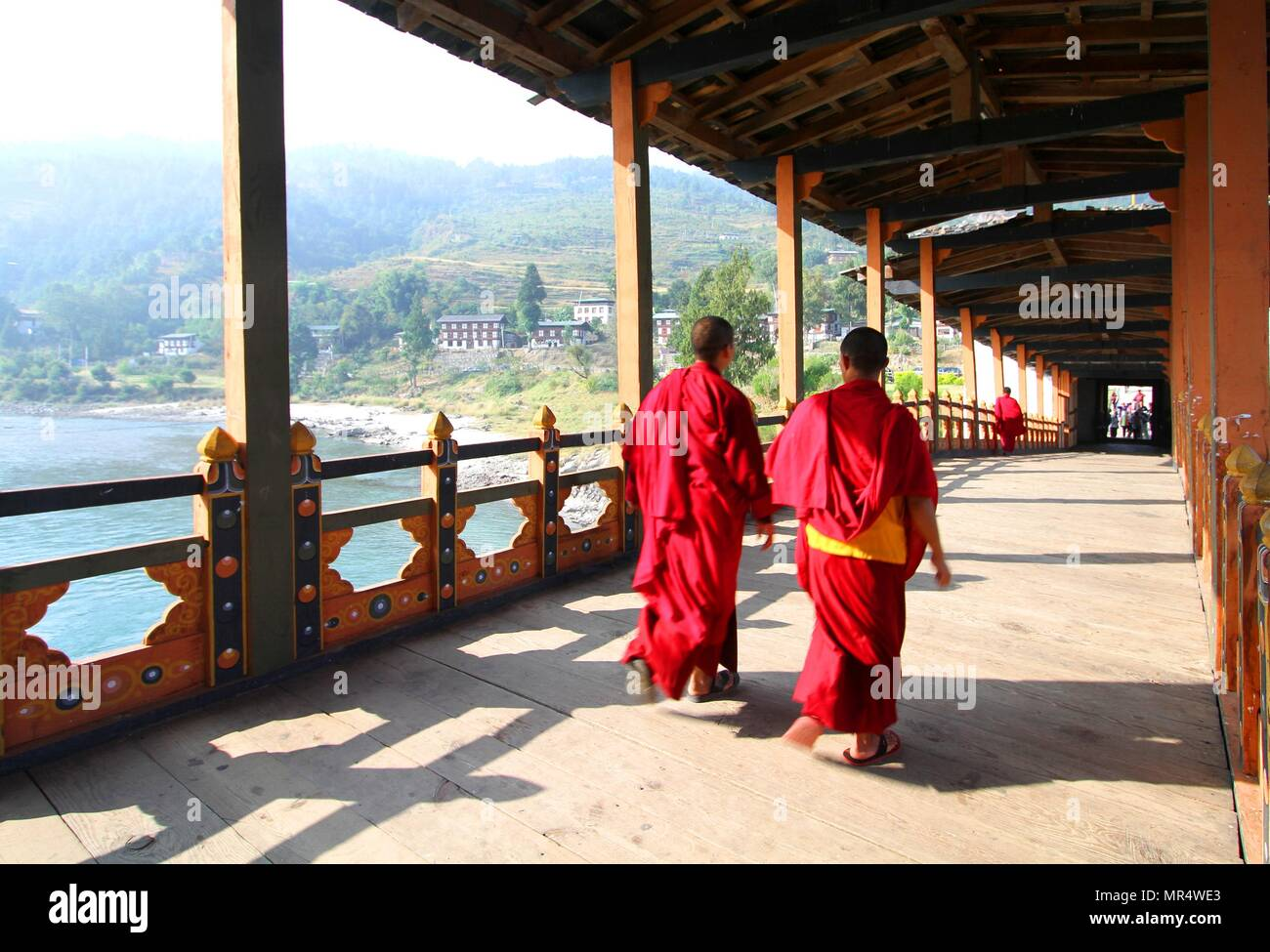 Two young monks walking on  PUNA MOCCHU BAZAM : Antique  wooden bridge at Punakha Dzong Monastery or Pungthang Dewachen Phodrang  Bhutan - Stock Image