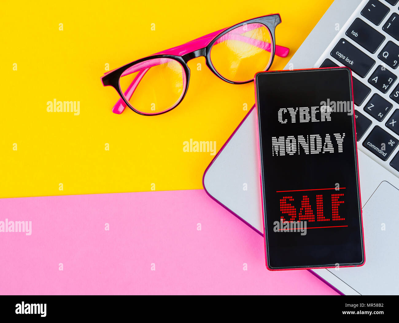 205ab8ccaa Cyber Monday sign on mobile phone over laptop with pink and yellow  background.