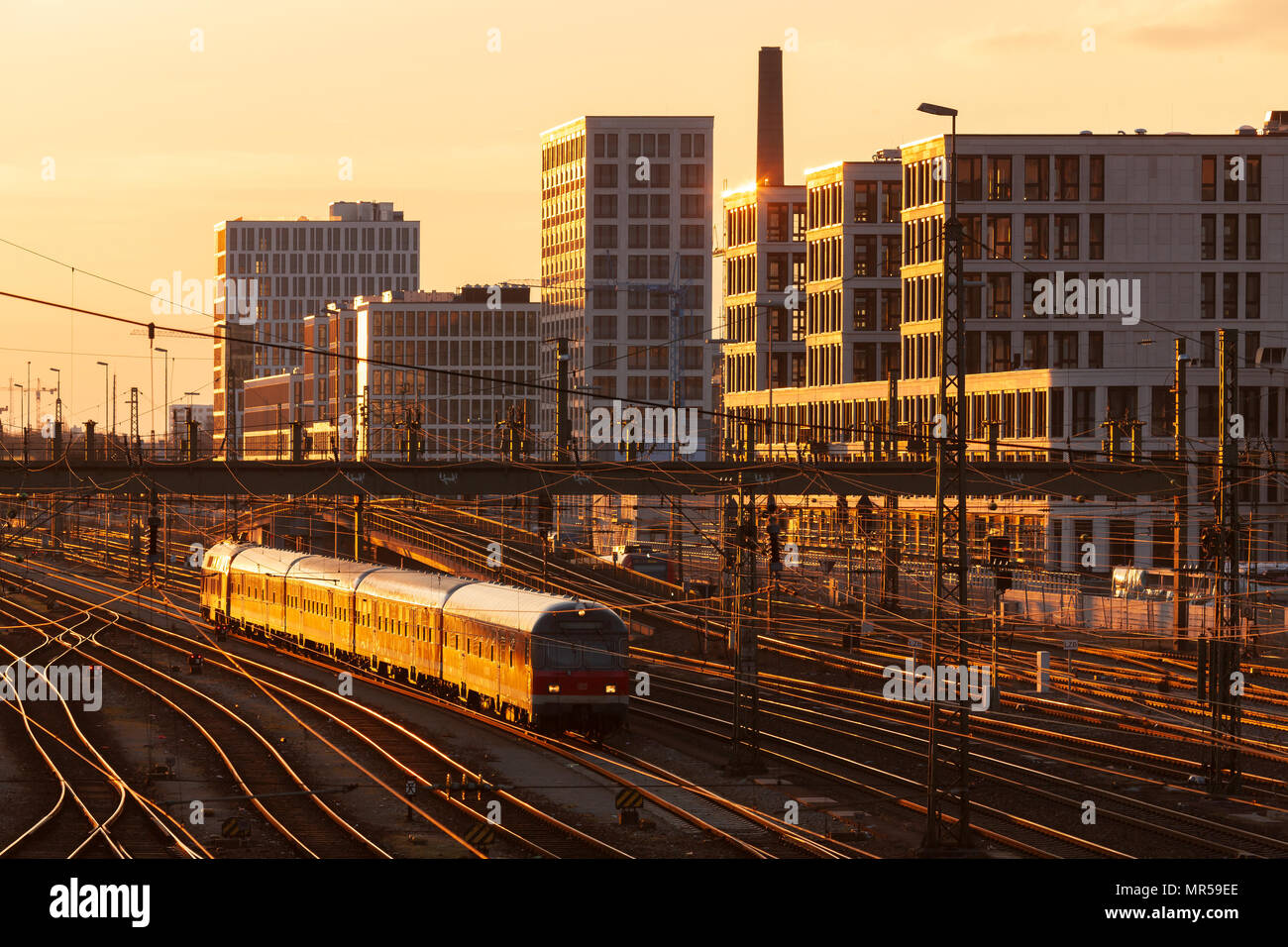 MUNICH / GERMANY: Track field of Munich Main Station with modern buildings in the background and a train in the foreground - Stock Image