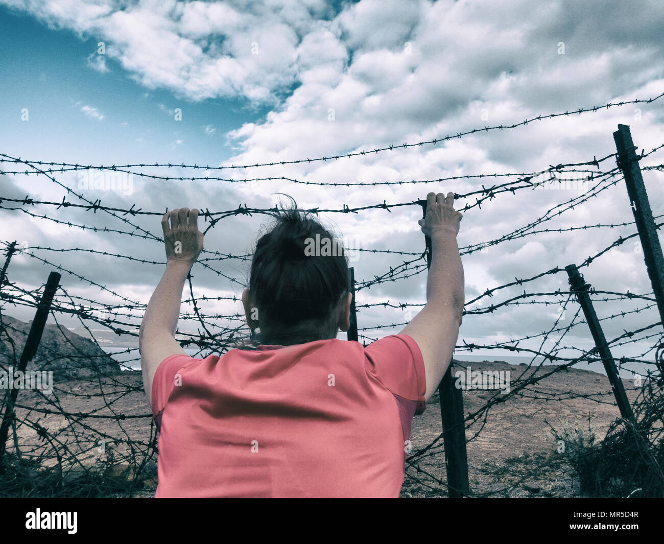 Woman behind barbed wire fence: asylum, Brexit, illegal immigration, human trafficking/slavery...,concept image. - Stock Image