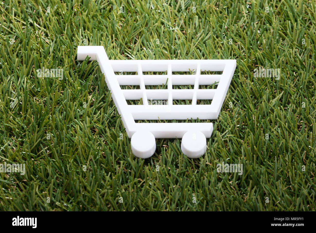 Elevated View Of White Shopping Cart On Green Grass Stock Photo