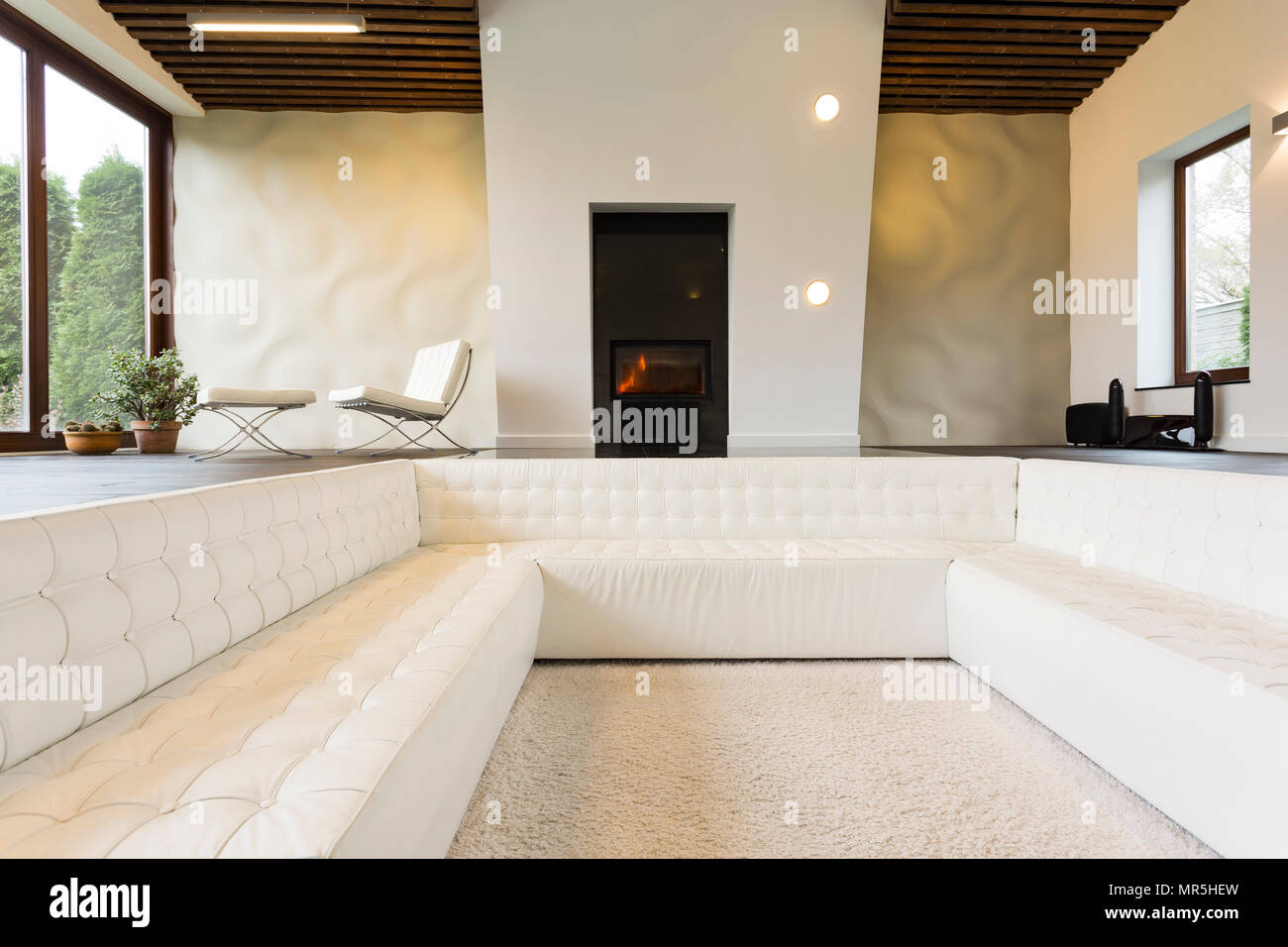 Luxurious lounge room with fireplace and white sofa Stock Photo