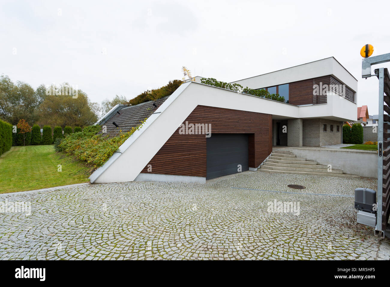 White and brown villa exterior with garden roof Stock Photo
