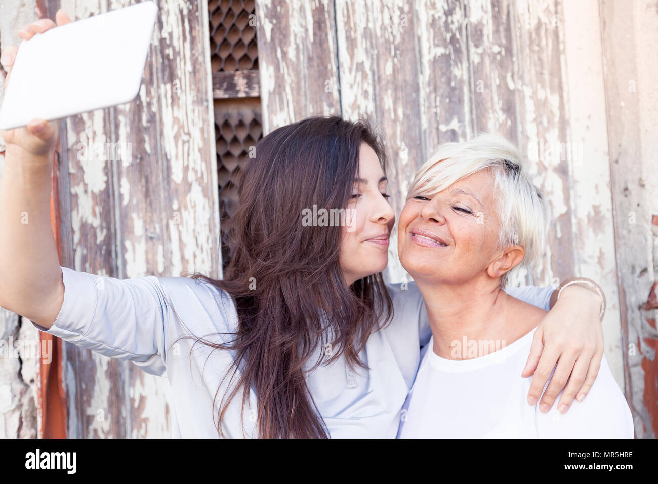 mother and adult daughter take a selfie outdoors - Stock Image