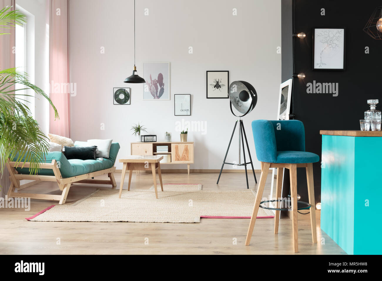 Blue barstool in kitchen area in warm room with turquoise settee with pillows and table on carpet - Stock Image