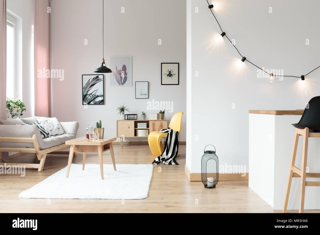 Lighting in bright living room with striped blanket on yellow chair ...