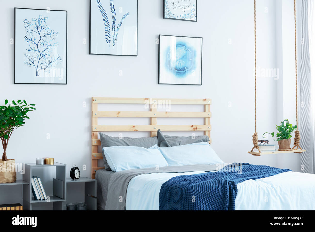 White bedroom with wood bed, swing shelf, wall posters, plants Stock ...