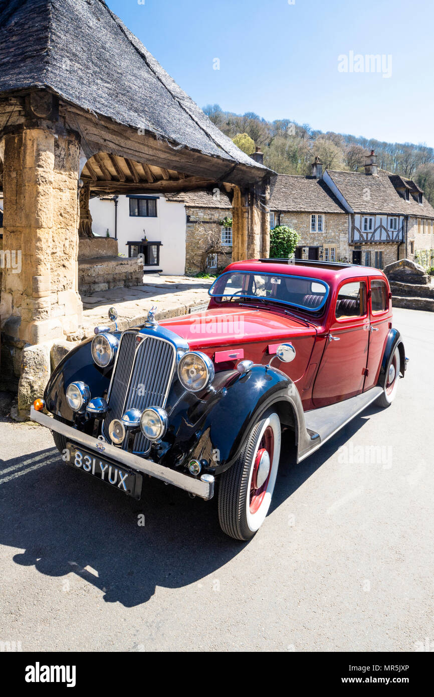 A red Rover 16 parked beside the market cross in the south Cotswold village of Castle Combe, Wiltshire UK - Stock Image