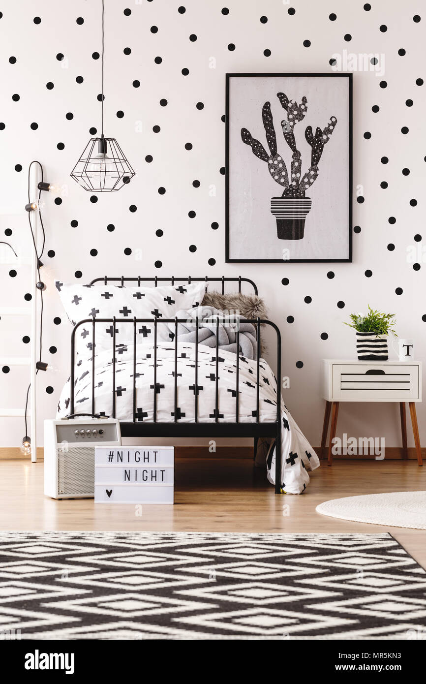 geometric carpet and simple poster in monochromatic kids room with white wallpaper with black dots MR5KN3