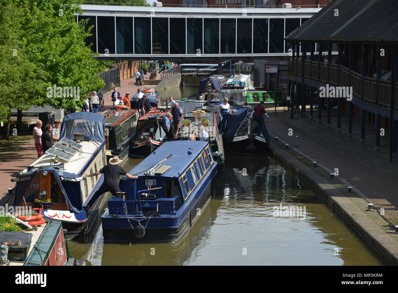 A traffic jam of narrowboats on the Oxford Canal outside Castle Quay Shopping Centre, Banbury, Oxfordshire. Efforts being made to separate the boats f - Stock Image