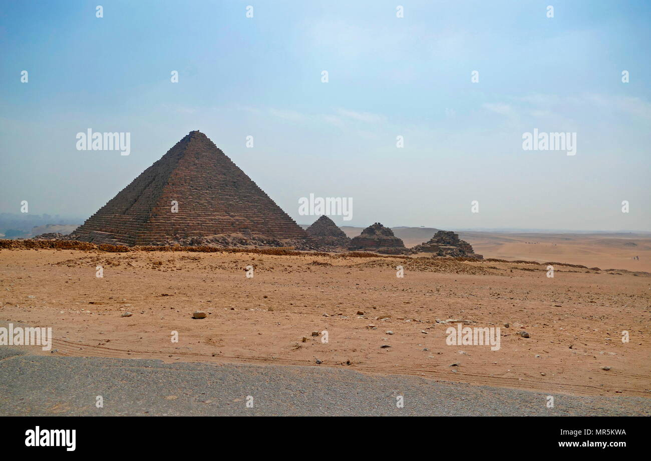 The Pyramid of Menkaure, on the Giza Plateau, Cairo, Egypt, is the smallest of the three main Pyramids of Giza. It is thought to have been built to serve as the tomb of the fourth dynasty, Egyptian Pharaoh Menkaure. circa 2500 BC. South of the pyramid of Menkaure are three satellite pyramids that are each accompanied with a temple and have a substructure - Stock Image