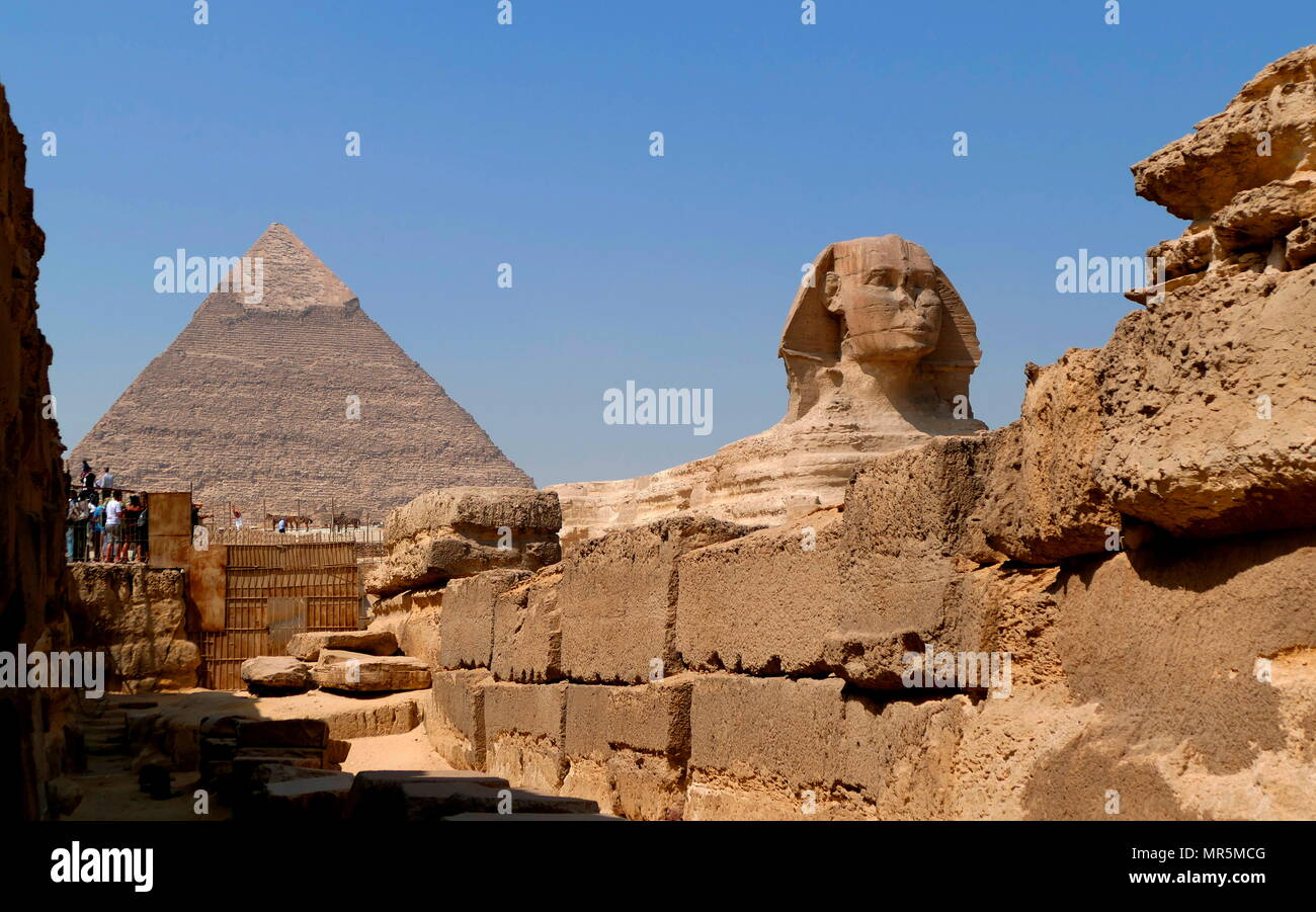 The Great Sphinx of Giza set against the  Pyramid of Khufu. limestone statue of a reclining sphinx, a mythical creature with the body of a lion and the head of a human. Facing directly from West to East, it stands on the Giza Plateau on the west bank of the Nile in Giza, Egypt. The face of the Sphinx is generally believed to represent the Pharaoh Khafre. Cut from the bedrock, the original shape of the Sphinx has been restored. It measures 238 feet (73 m) long (circa 2558–2532 BC). - Stock Image