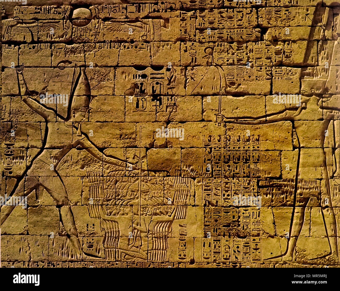 Medinet Habu, Mortuary temple of Ramses III. Relief depicting the king with captured Asiatic warriors before the god Amon-Re.  Twentieth Dynasty. Usimare Ramses III (also written Ramses and Rameses) was the second Pharaoh of the Twentieth Dynasty and is considered to be the last monarch of the New Kingdom to wield any substantial authority over Egypt 1186–1155 BC - Stock Image