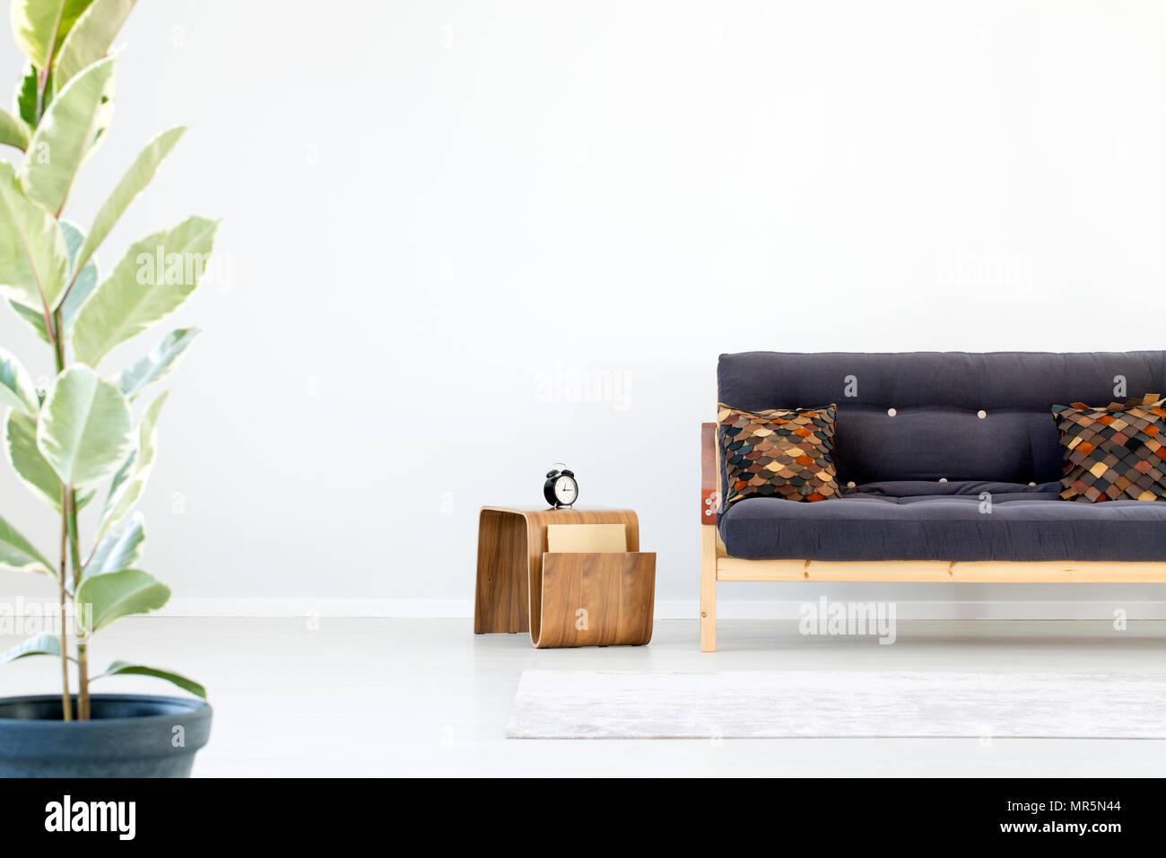 Clock on wooden table next to dark sofa with patterned brown pillows ...