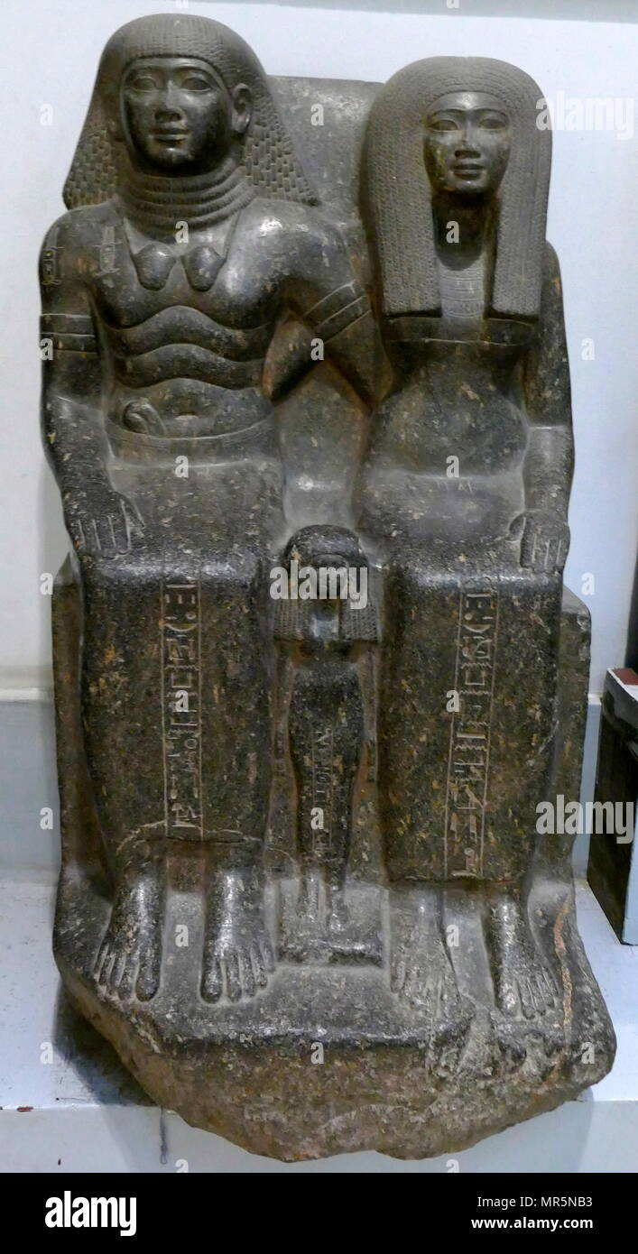 Granite statue depicting the Sennufer Mayor of Thebes, Sennay the royal nurse and their daughter Mut-Nofret. Karnak, Egypt. 18th Dynasty. The Ancient Egyptian noble Sennefer was 'Mayor of the City' (i.e. Thebes) and 'Overseer of the Granaries and Fields, Gardens and Cattle of Amun' during the reign of Amenhotep II of the 18th dynasty. Being a favourite of the king he accumulated great wealth. He was also allowed to place a double statue[1] of himself and his wife in the temple at Karnak - Stock Image