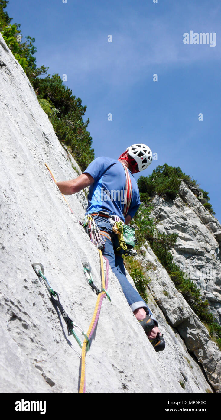 mountain guide climbing a steep slab pitch of a hard rock climbing route in the Alps of Switzerland Stock Photo