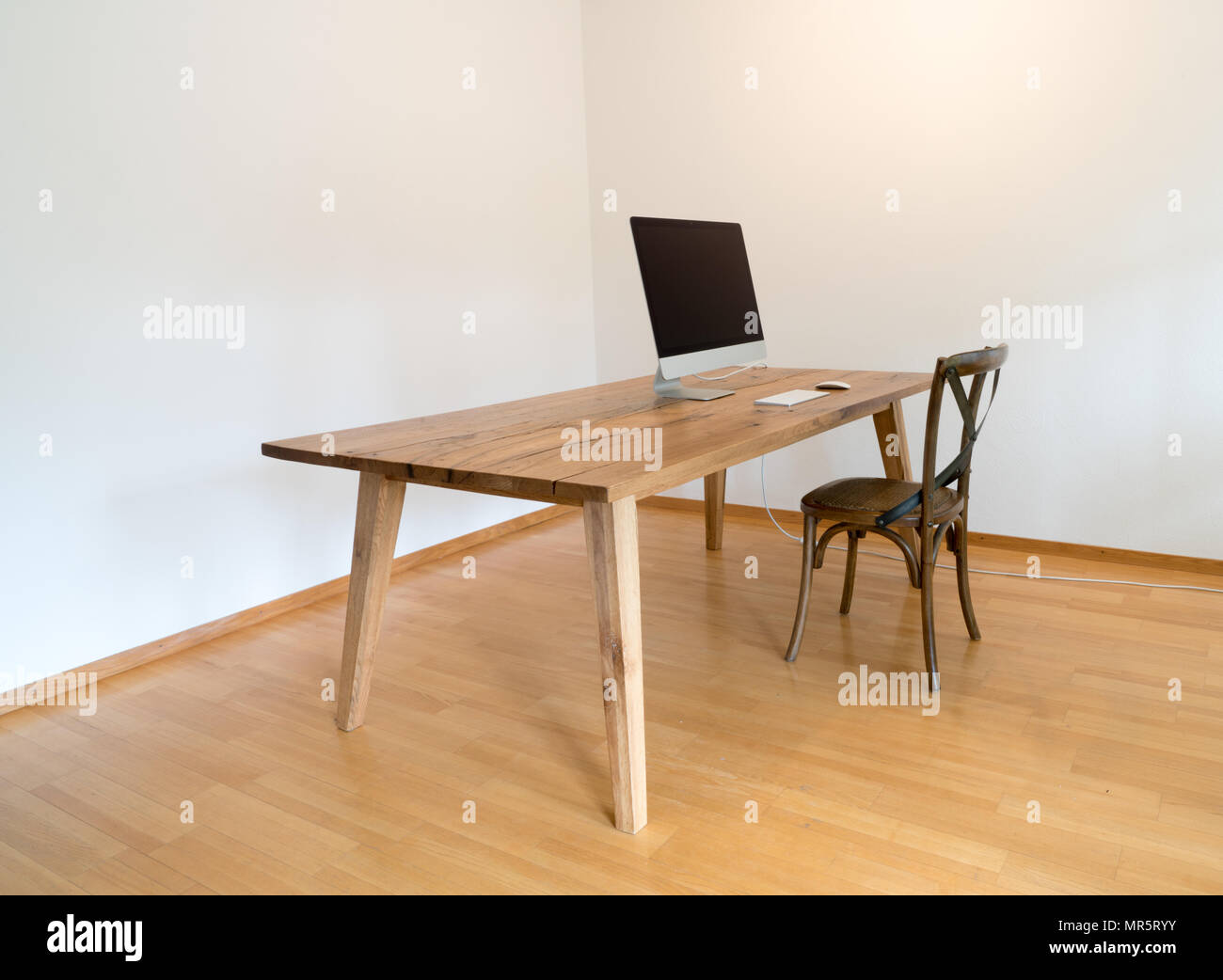 minimalist office with table and chair and computer - Stock Image