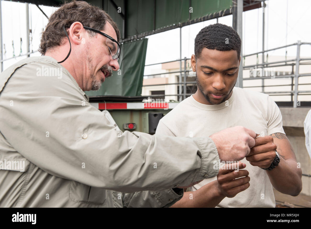 Larr Mudd, corrosion control trainer, shows U.S. Air Force Senior Airman Ladavian Varnes, 374th Logistics Readiness Squadron vehicle maintainer, a tool used to measure the thickness of applied solutions or paints to metal surfaces April 6, 2017, at Kadena Air Base, Japan. Varnes traveled from Osan Air Base to learn about and teach the 18 LRS's new vehicle corrosion control program. (U.S. Air Force photo by Senior Airman Omari Bernard) - Stock Image