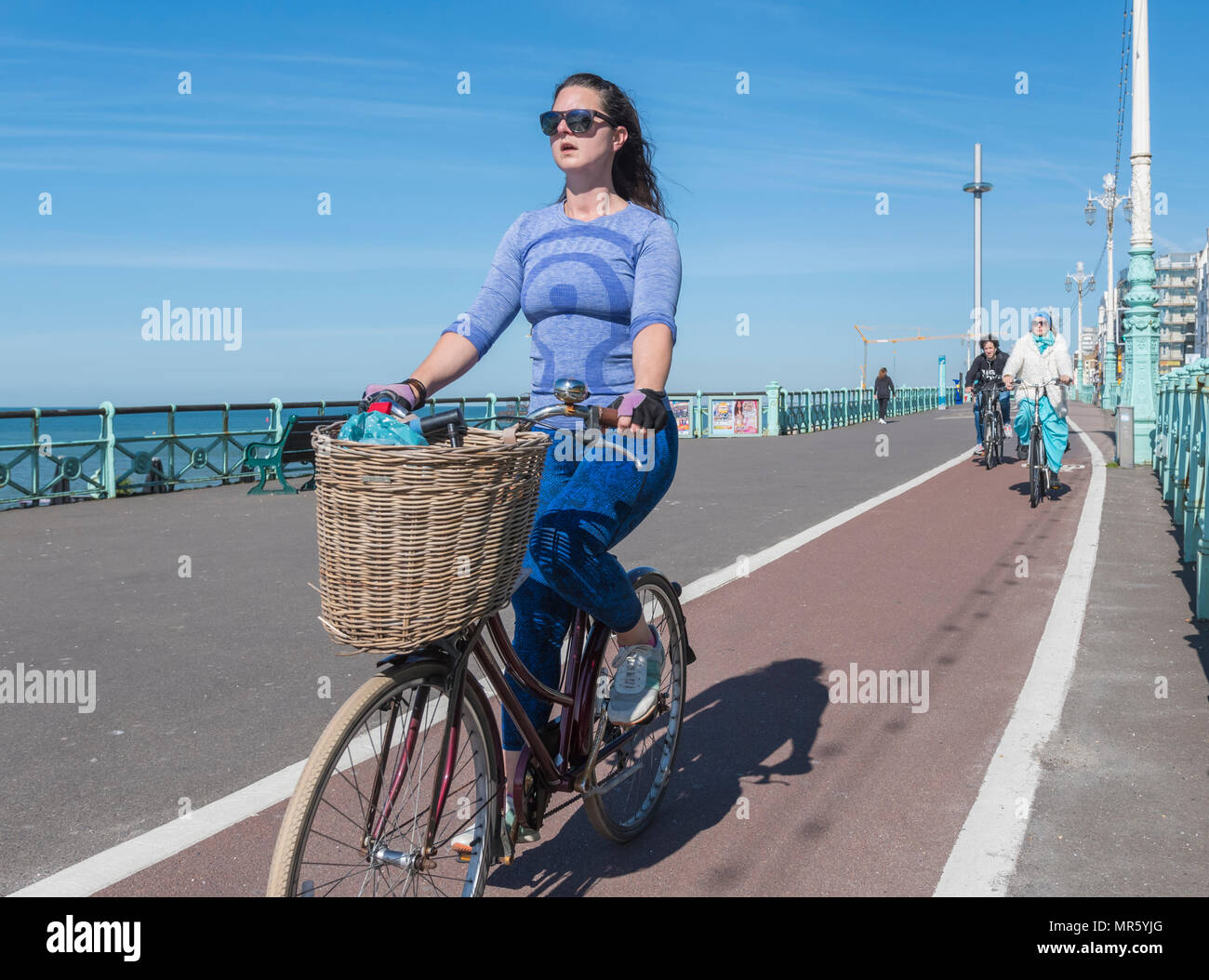 A woman cycling on a cycle path with a shopping basket, sitting upright with good posture on a bicycle lane in Brighton, East Sussex, England, UK. - Stock Image