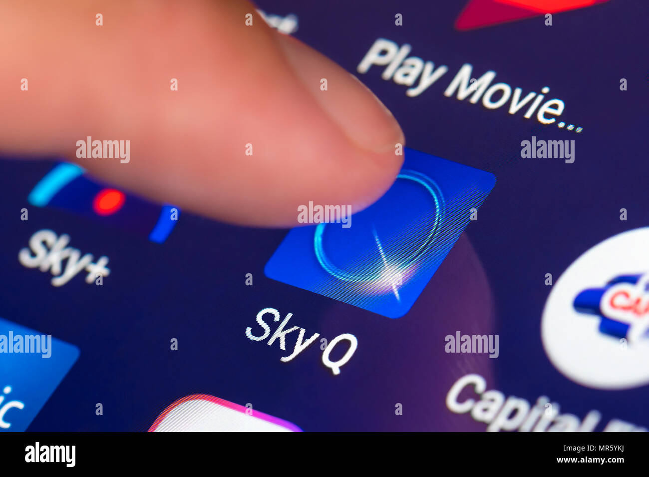 Finger pressing a Sky Q app icon on a mobile device or tablet. Sky TV on a tablet in the UK. - Stock Image