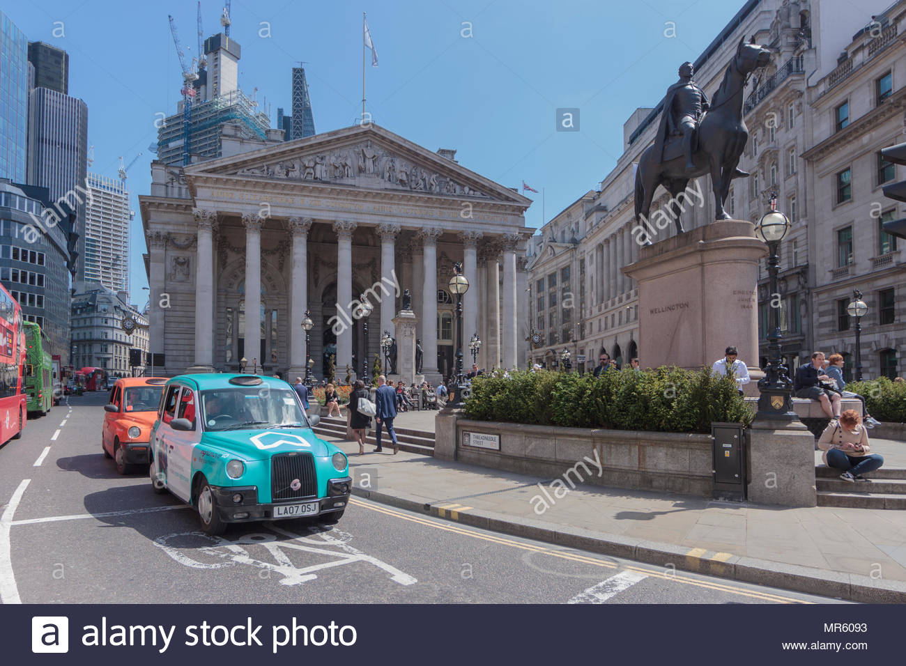 Threadneedle Street in the City of London. In the foreground is a London Hackney cab covered in blue advertising. - Stock Image