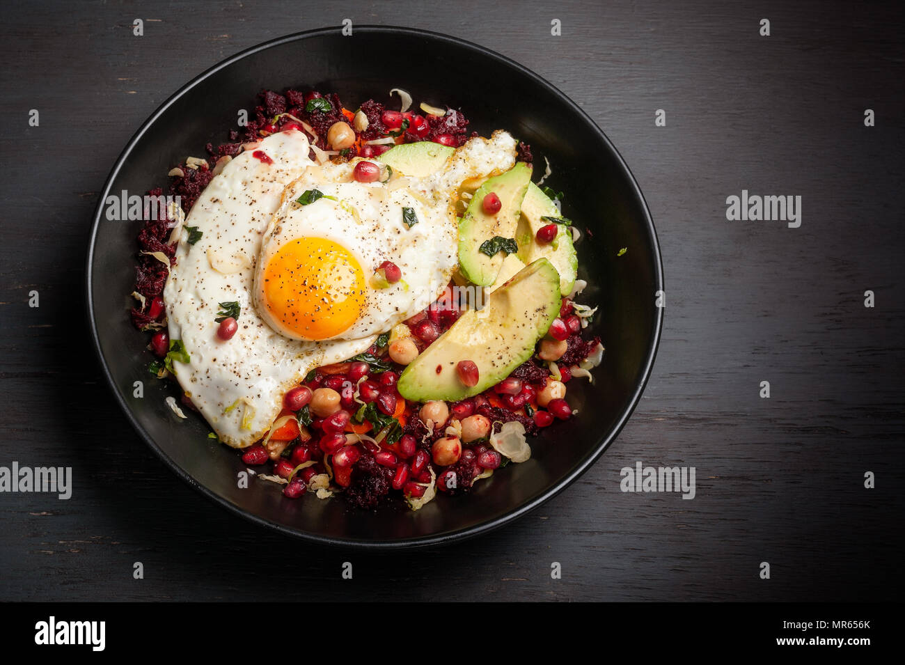 Miso veggie breakfast bowl made with beets, carrots, brussels sprouts, kale, chickpeas and topped with pomegranate seeds, avocado and egg. - Stock Image