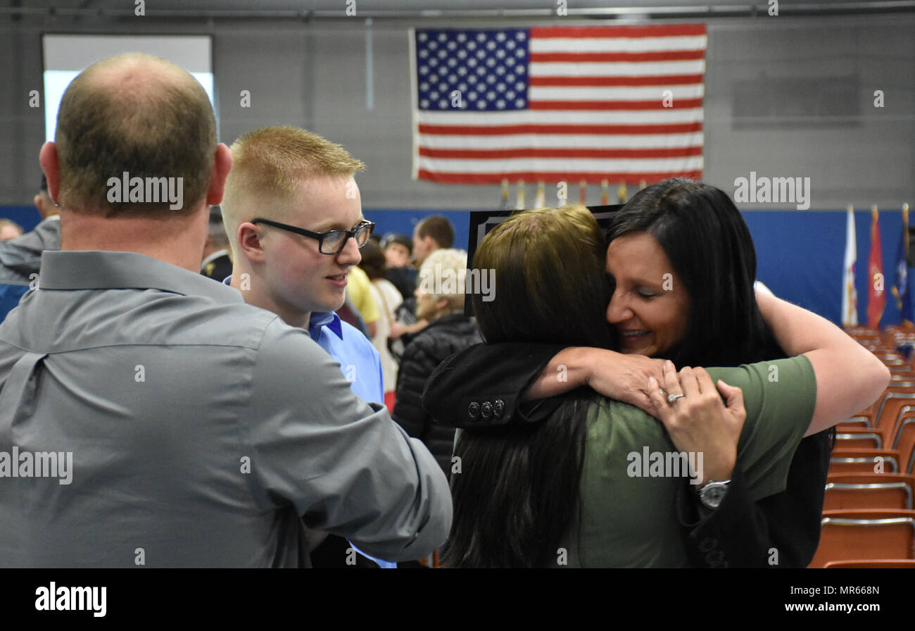 """A proud future U.S. Army Reserve mom hugs her daughter, Calista Lage, after she received an """"Our Community Salutes"""" certificate from Medal of Honor recipient Command Sergeant Major (Ret.) Kenneth E. Stumpf and Fort McCoy Senior Commander and 88th Regional Support Command Commanding General, Maj. Gen. Patrick Reinert during an """"Our Community Salutes"""" event at Fort McCoy, Wisconsin on Armed Forces Day, May 20, to recognize and honor graduating high school seniors who have committed to enlist in the Armed Forces following high school graduation. Stock Photo"""