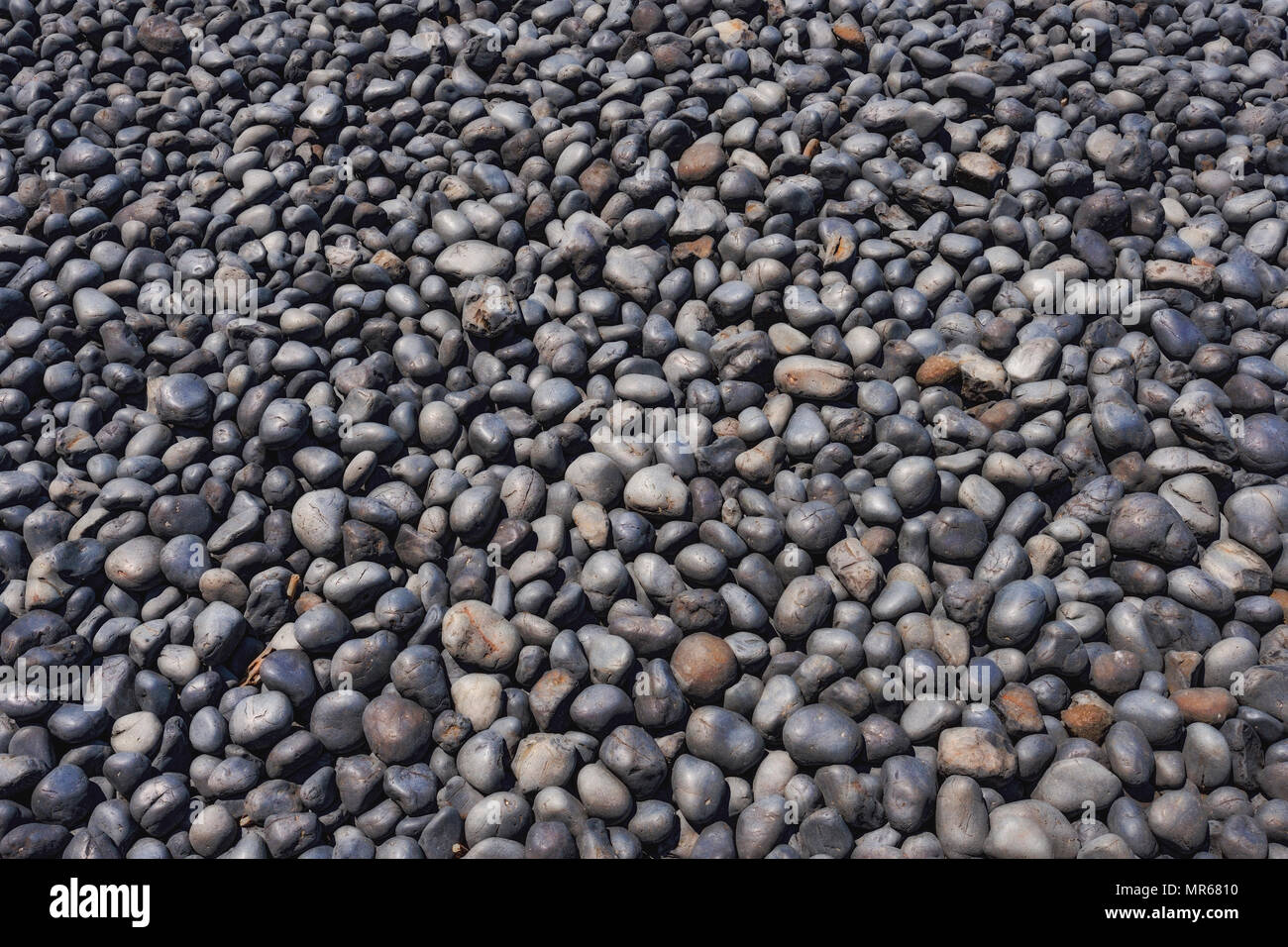 Clsoeup of cobble stones on Cobble Beach in Newport, Oregon.  The dark stones formed from lava being eroded over millions of years by the sea. - Stock Image