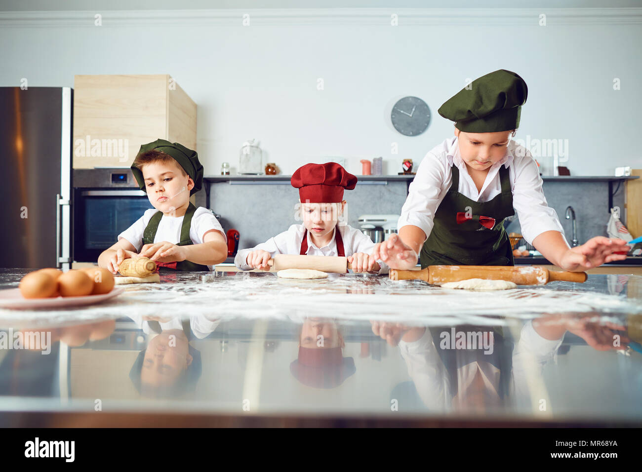 A group of children are cooking  in the kitchen. - Stock Image
