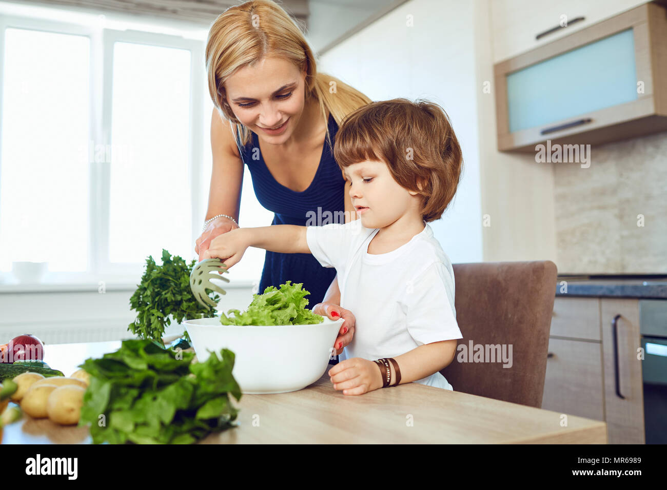 Mom and her child are preparing food in the kitchen.  - Stock Image