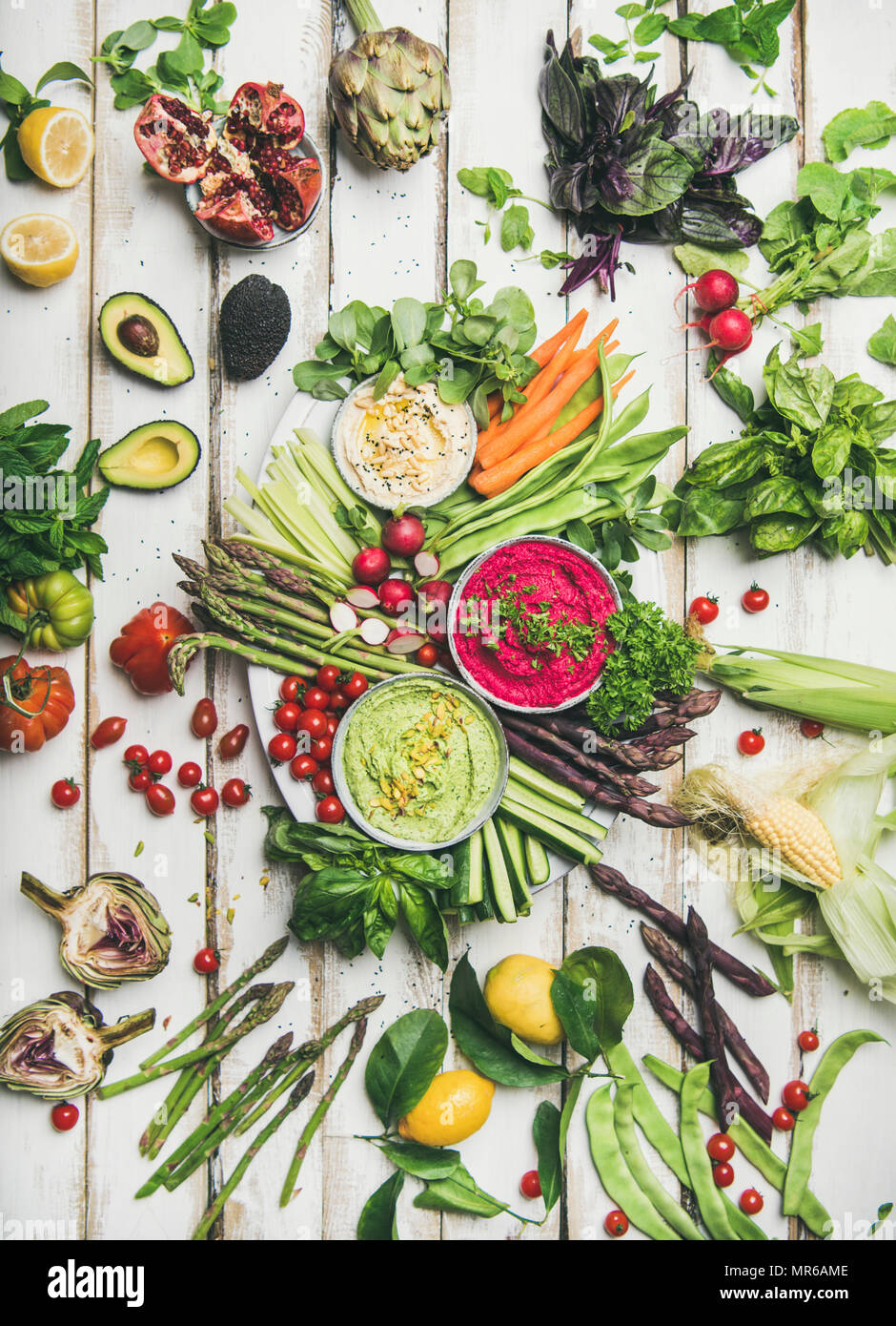 Healthy raw summer vegan snack plate. Flat-lay of chickpea, beetroot and spinach humus dips with colorful fresh vegetables and greens on white table b - Stock Image
