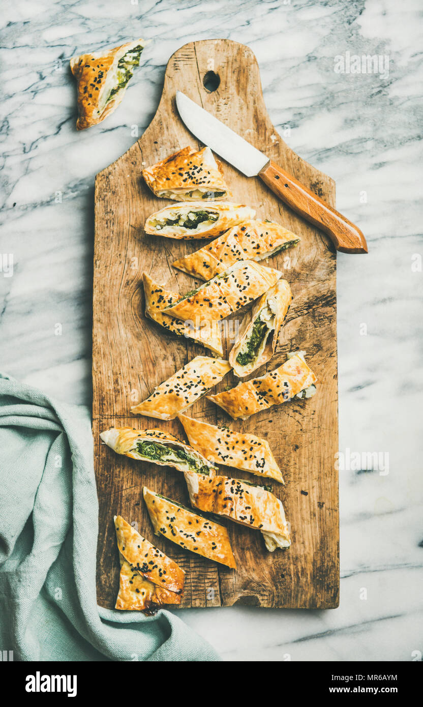 Flat-lay of fresh Turkish borek roll cut in slices slices with spinach, feta cheese, black cumin seeds on wooden board over grey marble background, to Stock Photo