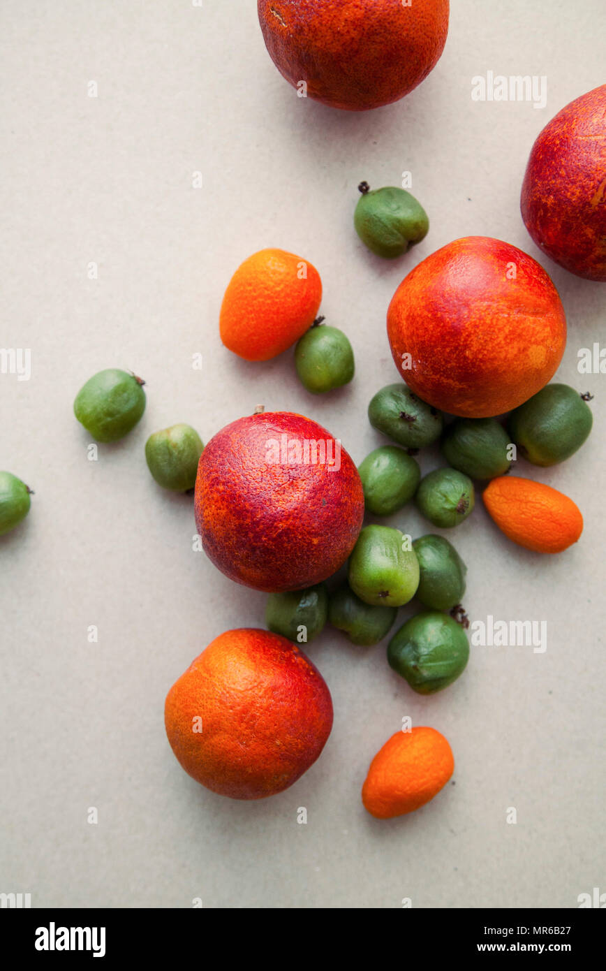 Varitety of fresh summer fruits on neutral background with mini kiwis and red oranges - Stock Image