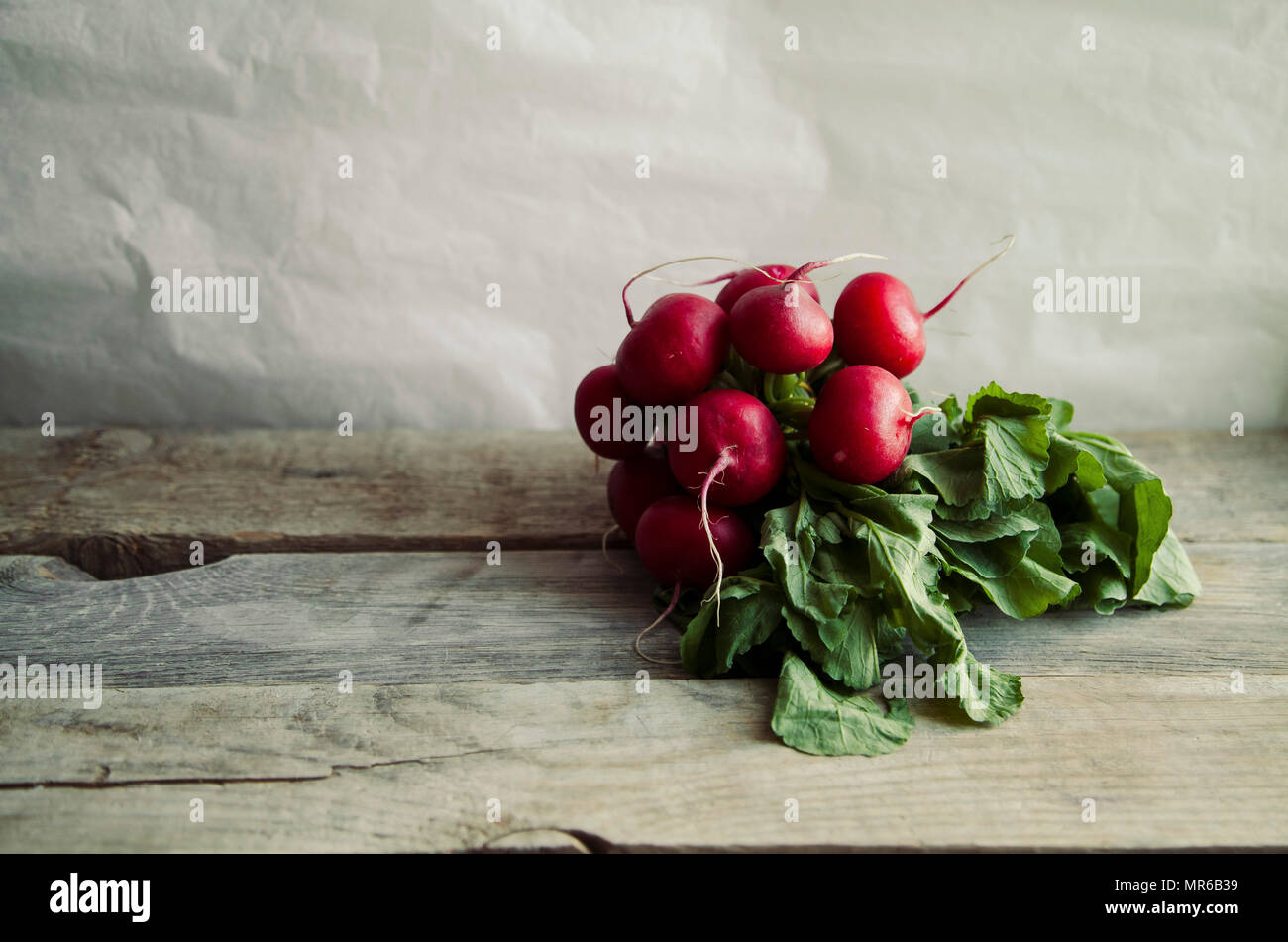 Heap of fresh radishes with tops and leaves on wooden rustic background with copy space - Stock Image