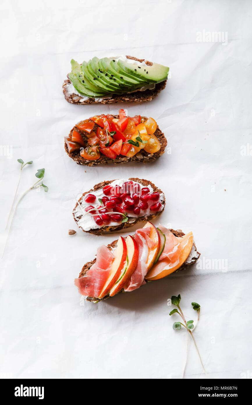 Variety of bruschettas with avecado, prosciutto, tomatoes and pomegranate seeds on white background Stock Photo