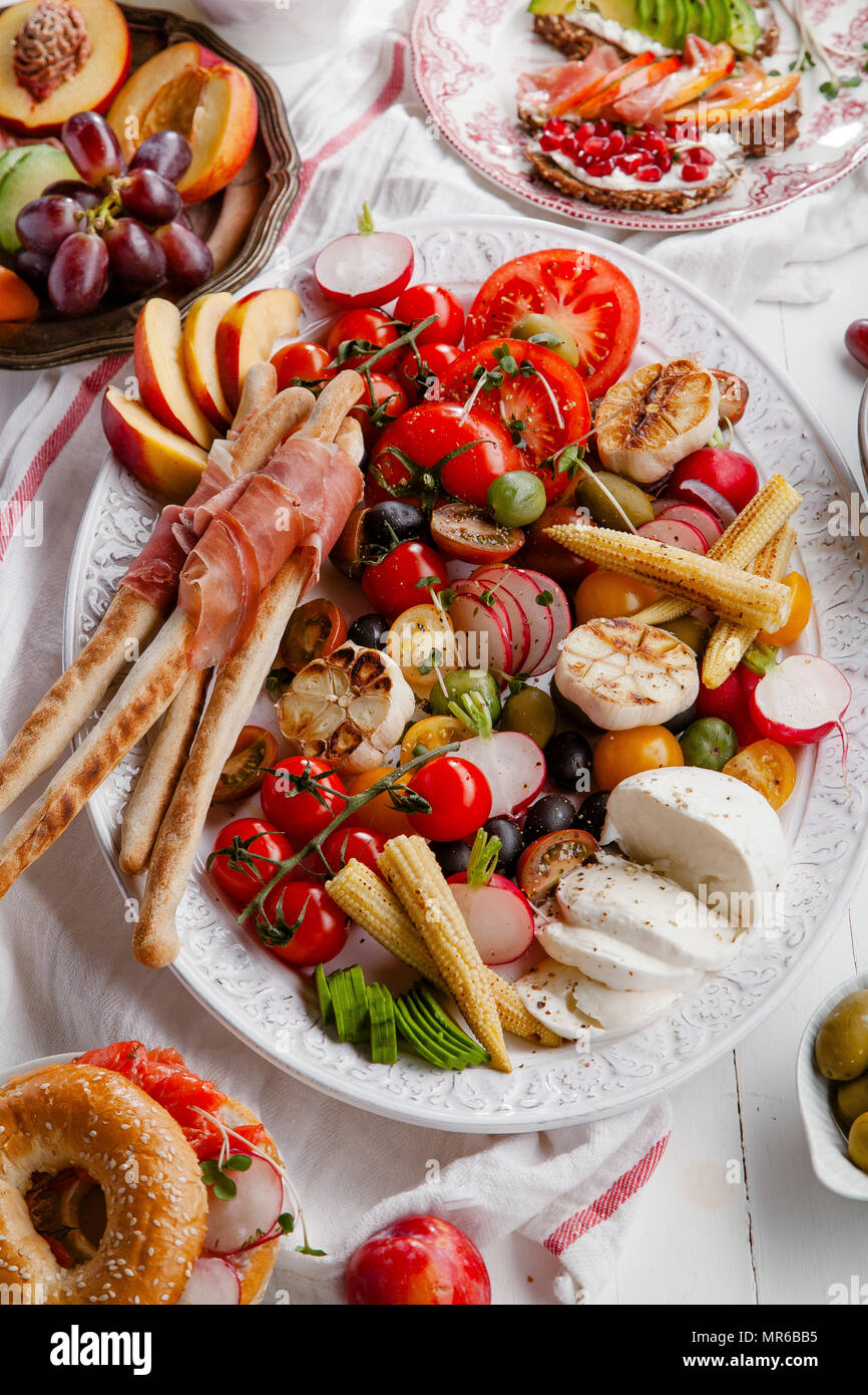 Variety of snacks prepared for picnic wine summer party with fresh fruits, vegetables, prosciutto and chesse - Stock Image
