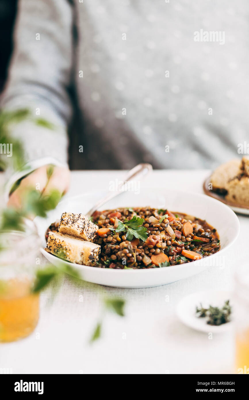 French Lentil Soup served on a table, with a woman seated - Stock Image