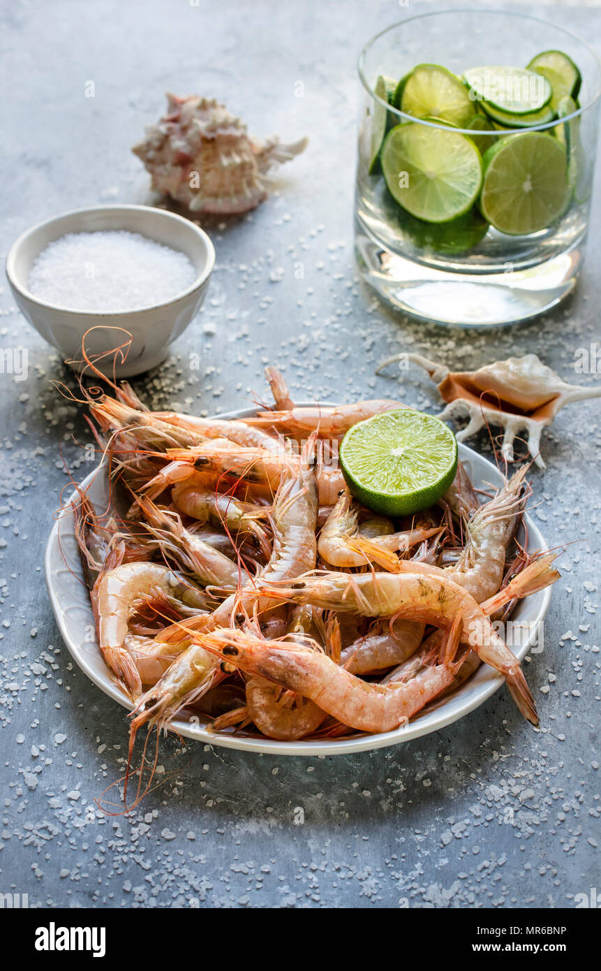 Fresh Shrimps in a bowl with lime - Stock Image