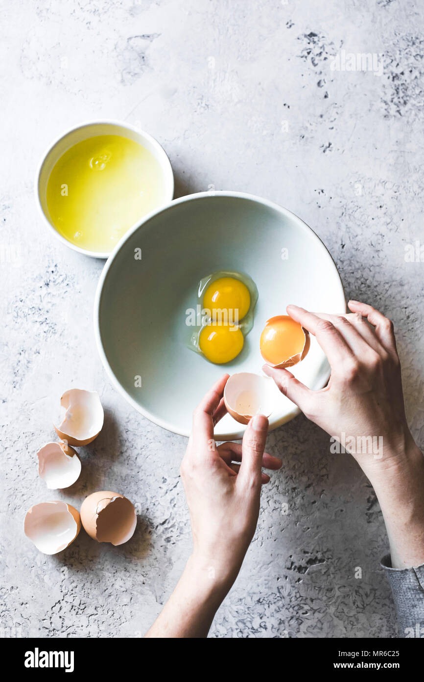 A womans hands separating eggs whites from egg yolks, with a mixing bowl - Stock Image