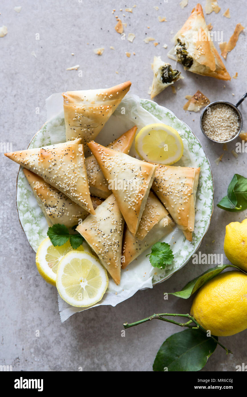 Spanakopita triangles or spinach pie is a Greek savoury pastry. Ingredients include spinach, feta cheese, onions and eggs. - Stock Image