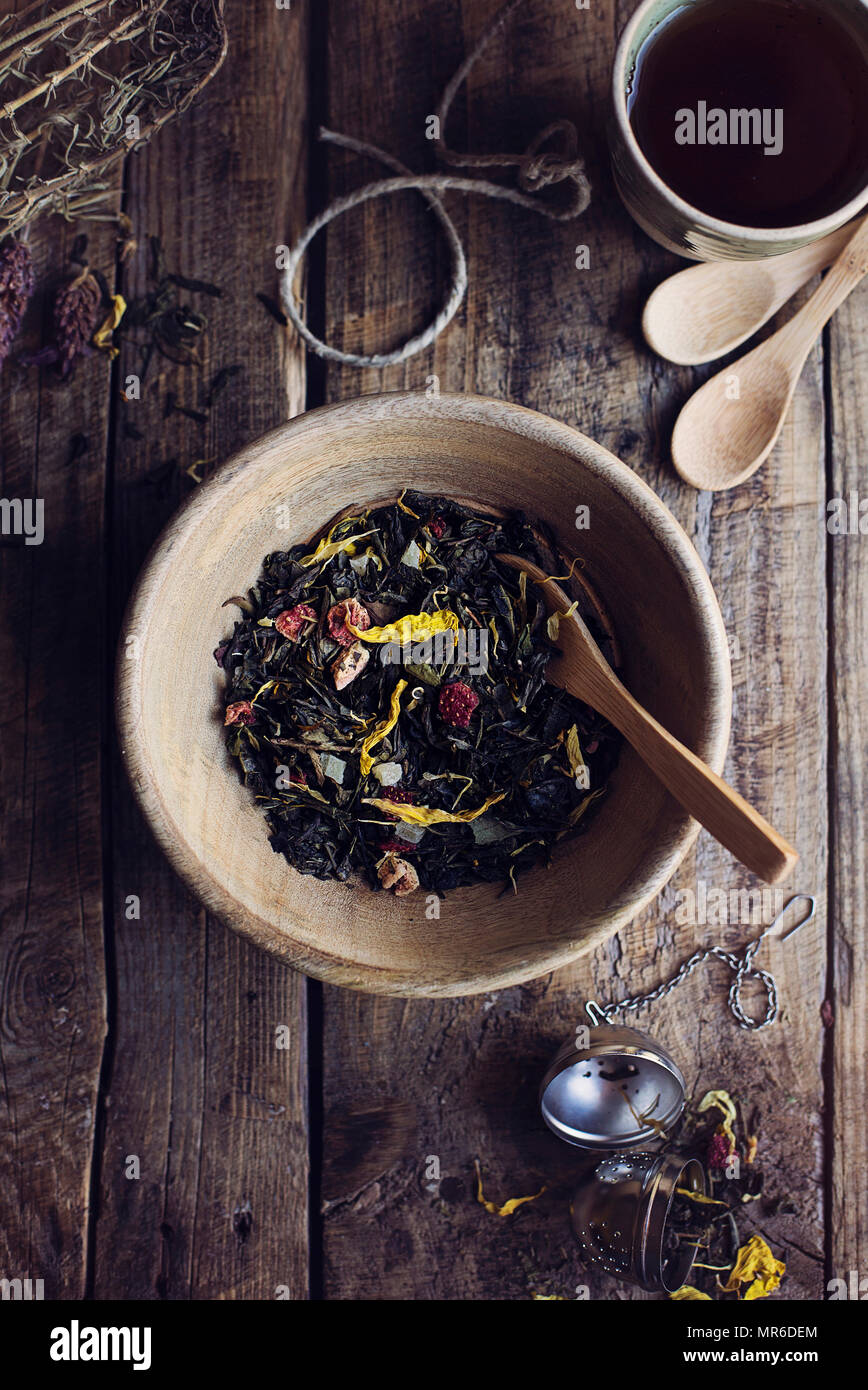 Herbal dry tea leaves with wild flowers and dried fruit on wooden rustic table. Top view - Stock Image